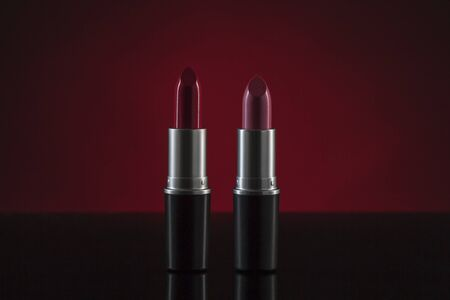 Red and pink lipstick with clipping path standing against dark background