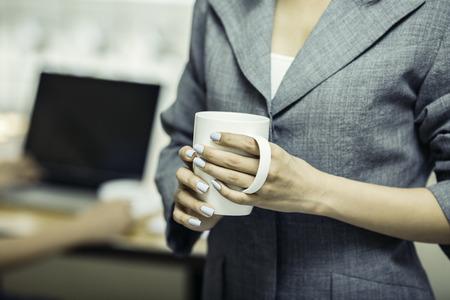 Partie du corps de la femme tenant une tasse de café Banque d'images - 74469708