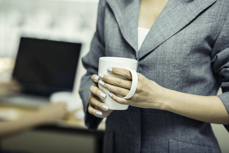Part of woman body holding a coffee cup Standard-Bild