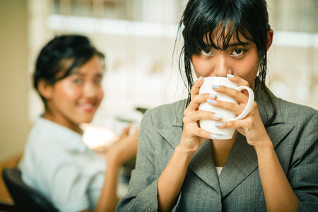 Smiling businesswoman enjoy drinking coffee in office Banco de Imagens