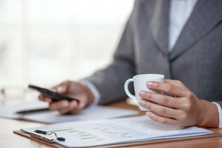 Femme d'affaires faisant un appel téléphonique et boire du café Banque d'images - 75548231
