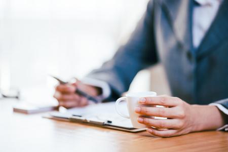 Ein Geschäftsfraugetränkkaffee beim Arbeiten im Büro Standard-Bild - 75548193