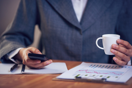 Businesswoman text messaging in office and holding coffee cub