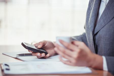 Femme d'affaires surfer sur internet sur smartphone et tenant un café Banque d'images - 75548183