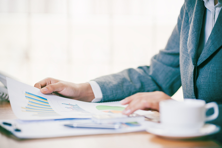 Businesswoman calculating and analyzing business chart