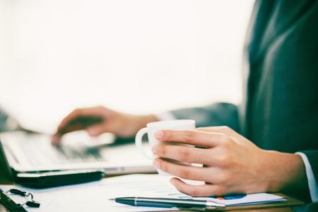 Une femme d'affaires travaille avec un ordinateur et boit du café Banque d'images - 75548176