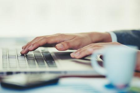 Femme au bureau et travaille sur son ordinateur portable Banque d'images - 75548128
