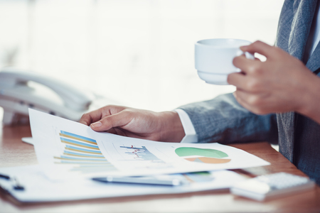 Business person reading financial graph and drink coffee Standard-Bild