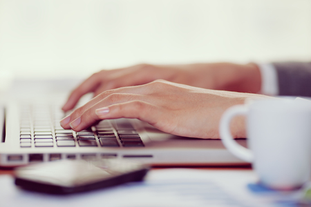 Woman hand typing on her laptop in office