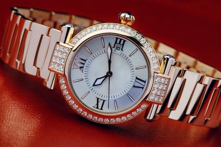 Goldene Luxusarmbanduhr verziert mit Diamanten gegen roten Hintergrund Standard-Bild - 76996252