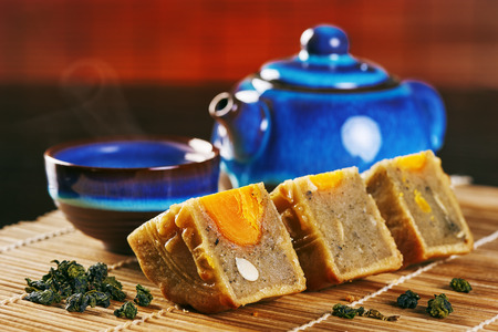 Delicious moon cake stacked in pieces with tea pot