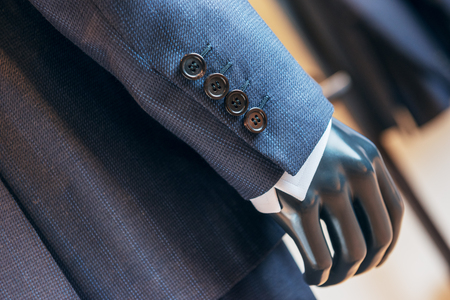 Closeup of suit sleeve and button in dark blue color