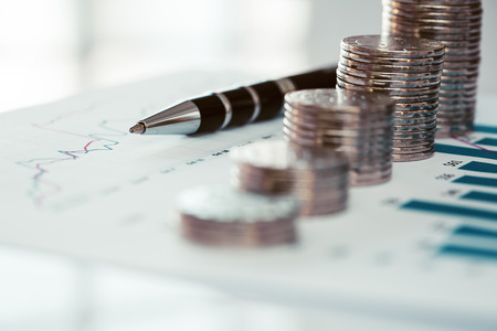 Stack of coins with financial line chart and pen Standard-Bild