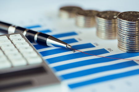 Stack of coins with bar chart, pen and calculator Standard-Bild