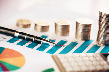Coins with financial chart, pen and calculator