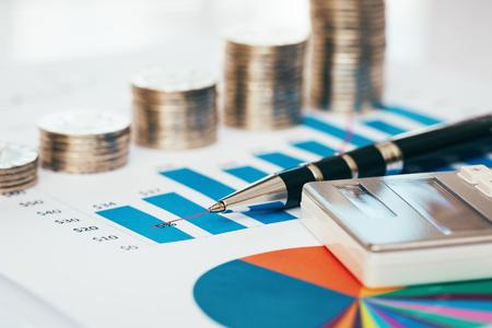 Pile de pièces avec tableau financier, stylo et calculatrice Banque d'images - 78177907