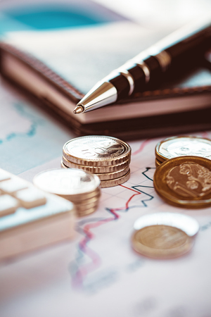 Vertical closeup coins on line chart with pen and calculator