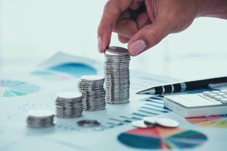 Geschäftskonzept des Einsparens des Geldes mit Münzen und Diagramm Standard-Bild - 78471966