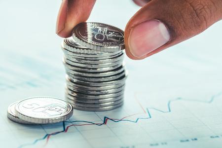 Tenant une pièce de monnaie sur les pièces de monnaie et graphique financier Banque d'images - 80935898