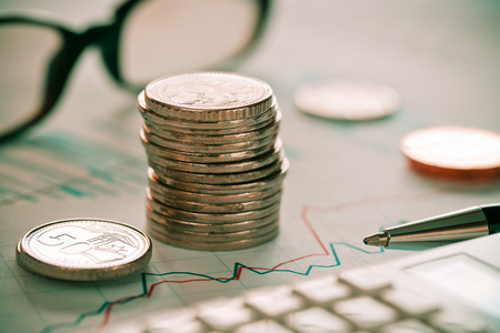 Concept of writing and analyzing stock market combination with glasses and coins