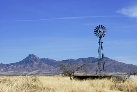 Spinning windmill in a winter field before a rugged mountain range under a partly cloudy sky. photo