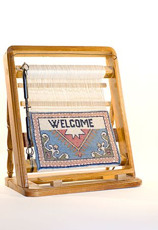 Wooden frame loom with the start of a woven welcome tapestry. photo
