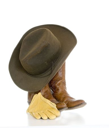 cowboy boots: Still life of a brown cowboy hat hanging from light brown cowboy boots with leather gloves alongside isolated over white.