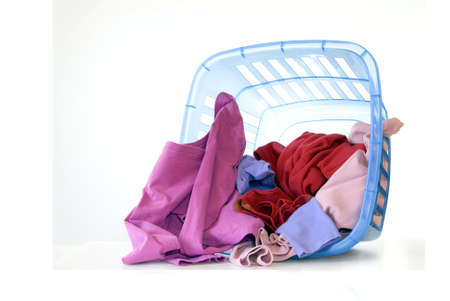 Colorful dirty laundry spills from a toppled over blue laundry basket isolated over a white background. photo