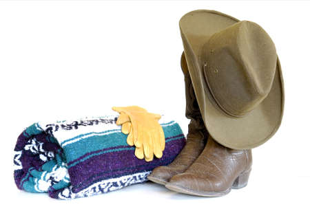 Still life of a brown cowboy hat hanging from brown cowboy boots with leather gloves atop a green, purple and white blanket isolated over white. photo