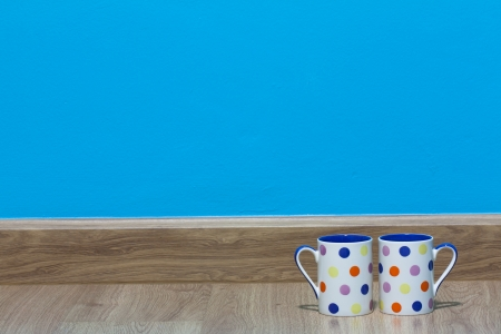 Two blue polka dot cups on wood floor in blue room background