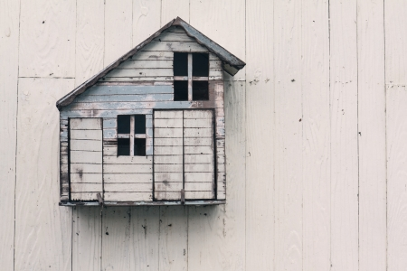 model of handmade wood home on white wooden wall