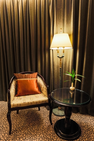 Luxurious hotel room interior with wooden chair and lamp