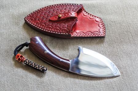 scabbard: Tailandesa cuchillo de caza rojo con vaina de cuero en la tela de fondo marr�n