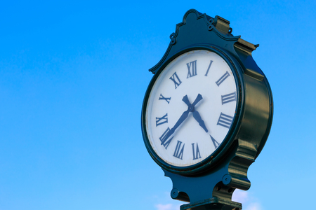 roman pillar: Retro green clock on pillar with roman numerals and blue sky background Stock Photo