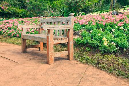 relax garden: Wooden bench in flowers garden