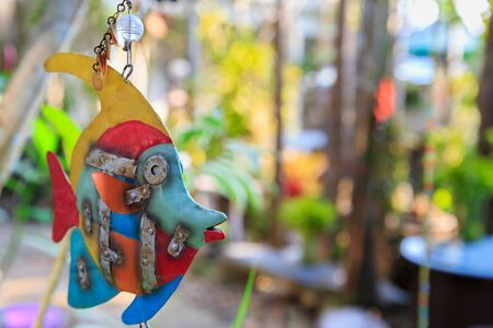 chaetodontidae: Fish ornament hanging on a tree with bokeh background Stock Photo