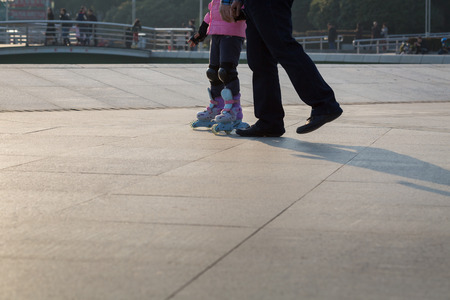 roller blade: Father and daughter holding hand in hand to play roller blade