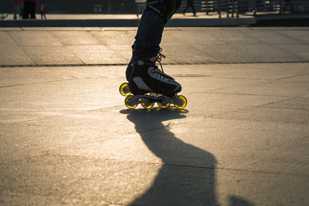 roller blade: Closeup of boy playing roller blade in park with sunset light Stock Photo