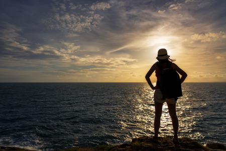 koh samet: Backpack traveler asia woman standing on sea cliff in sunset Koh Samet Rayong Thailand