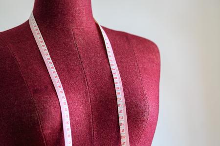 mannequin: Violet mannequin de v�tements avec un ruban � mesurer sur le ciment blanc fond mur