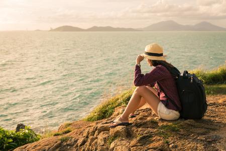 koh samet: Backpack traveler asia woman sitting on sea cliff in sunset, Koh Samet, Rayong, Thailand