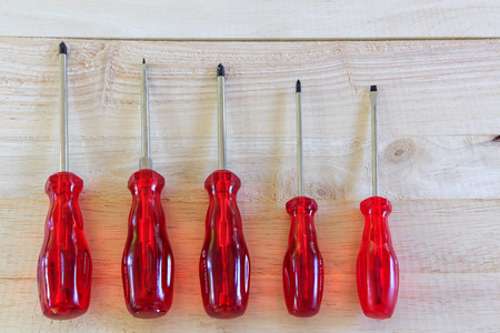 screwdrivers: Red screwdrivers on wooden background
