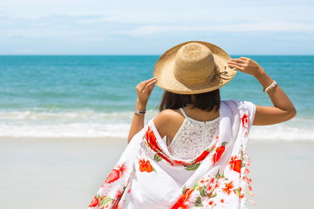 Back view of Travel asia woman with hat and dress looking out of sea on a beach in summer, Koh Samet, Thailand