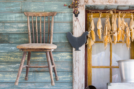 drying corn cobs: Wooden chair and dry corn cob hanging on window of farmhouse with garden tool Stock Photo