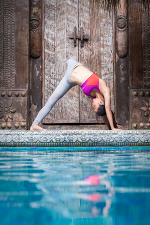 Asia woman doing yoga fitness exercise for relax and healthy beside swimming pool background, Concept outdoor sport and health Stock Photo