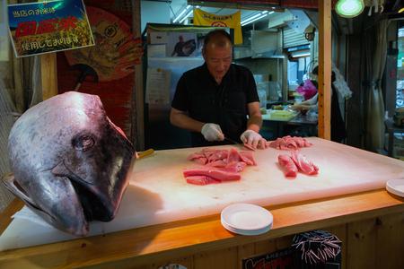 atun rojo: OSAKA - JUN 8, 2016: corte del cocinero atún rojo en Kuromon Mercado, Japón Editorial