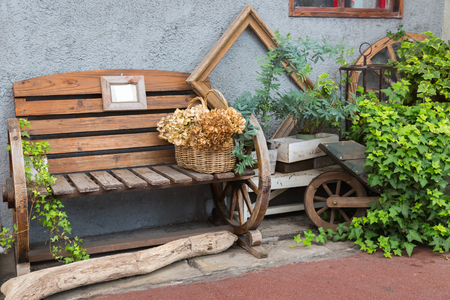 country house style: Decoration of faemhouse style with bench and Wicker basket in garden Stock Photo