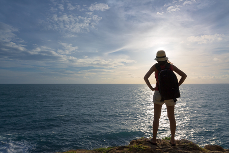 Backpack traveler asia woman standing on sea cliff in sunset, Koh Samet, Rayong, Thailand Stock Photo