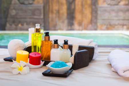 swimming candles: Spa massage setting product with candles, towel, treatment and salt in thai style resort pool view Stock Photo