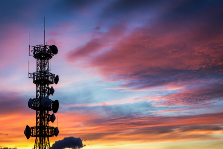 Silhouette of the Antenna on communication system tower with sunset sky background Zdjęcie Seryjne